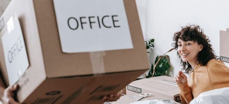 """man carrying an """"office"""" labeled cardboard box"""