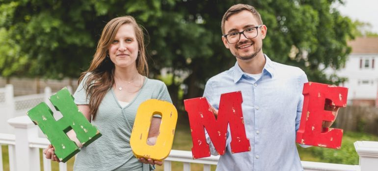 couple holding a home sign