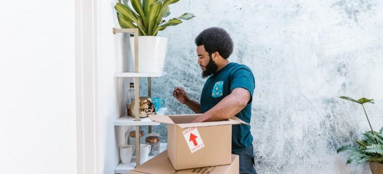 A man in a blue shirt placing items in the box.